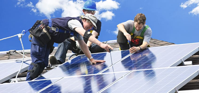 Solar installation on a roof with workers